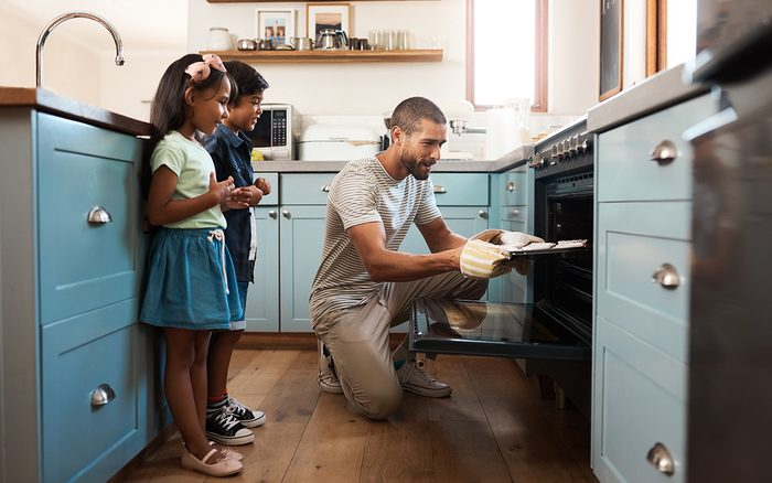 Shot of a young man baking at home with his two young kids