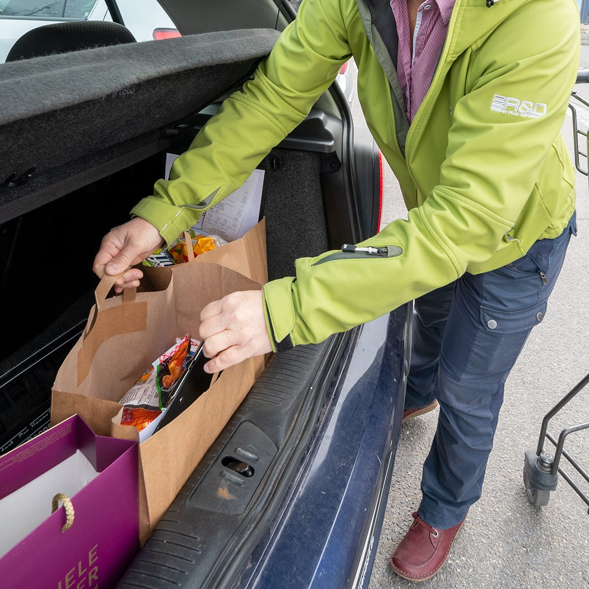 "26 March 2020, Bavaria, Deggendorf: An assistant puts a bag of food in a trunk. The woman provides food for the elderly and sick. (to dpa-Korr """"Happy that something like this exists"" - shopping help for the elderly and sick"") Photo: Armin Weigel/dpa (Photo by Armin Weigel/picture alliance via Getty Images)"