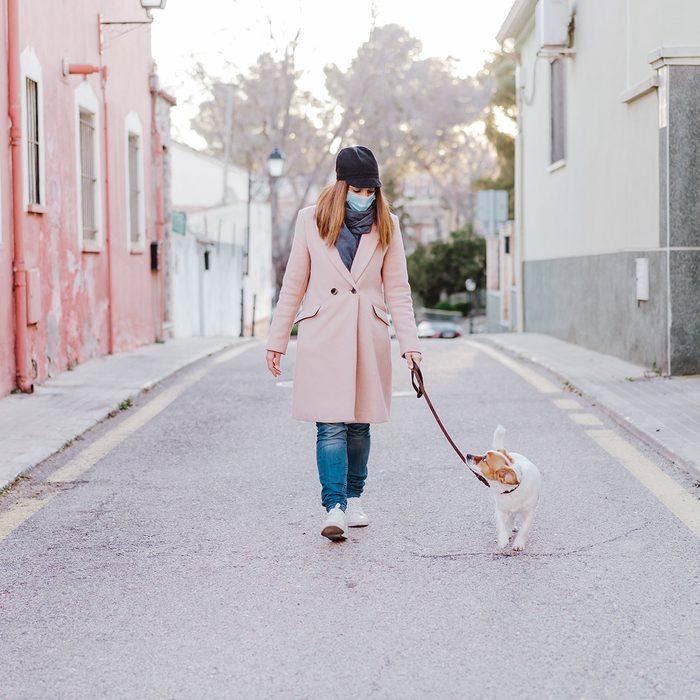 Woman wearing a face mask walking a dog