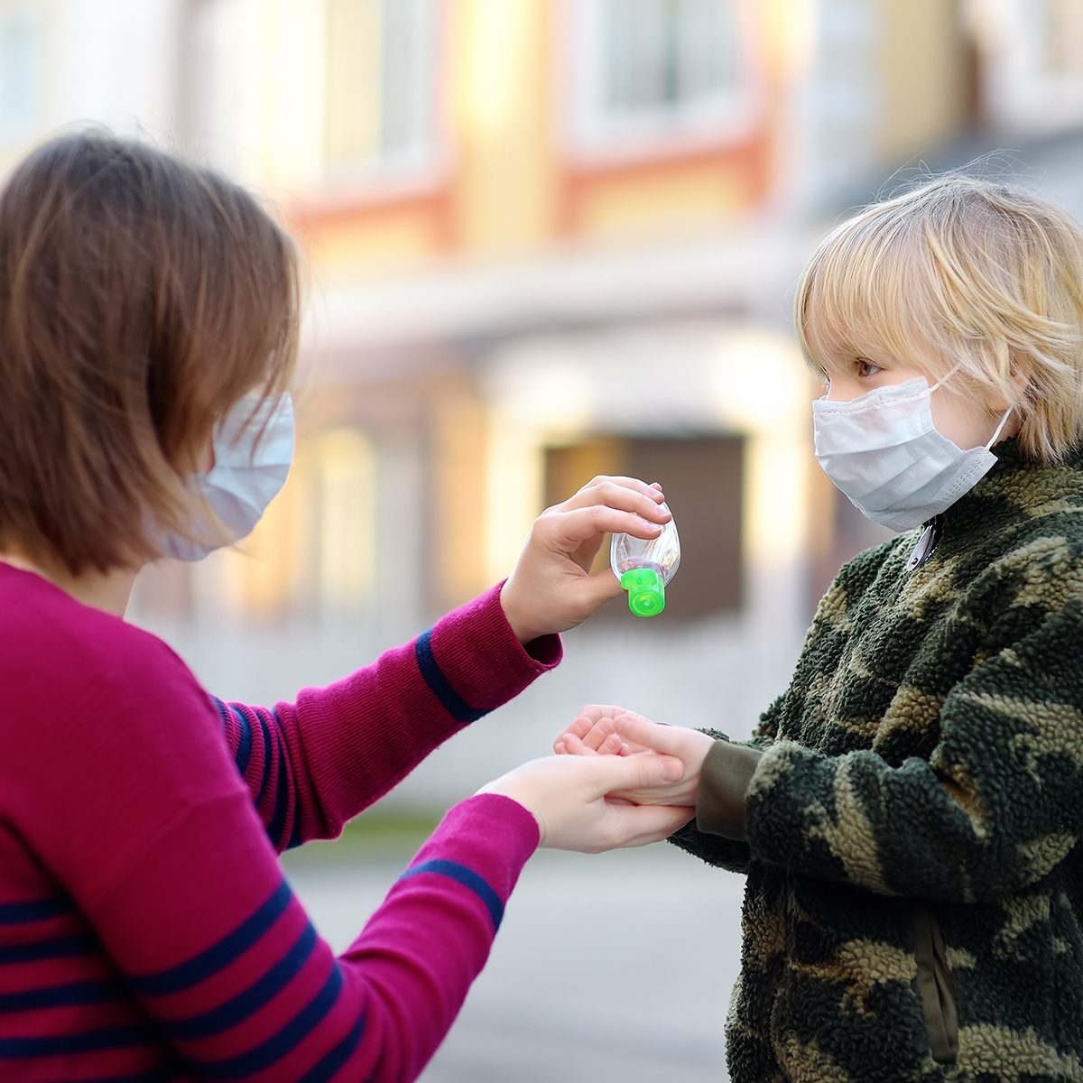 Young woman and little child wearing protective mask makes disinfection of hands with sanitizer in airport, supermarket or other public place. Safety during COVID-19 outbreak. Epidemic of virus covid