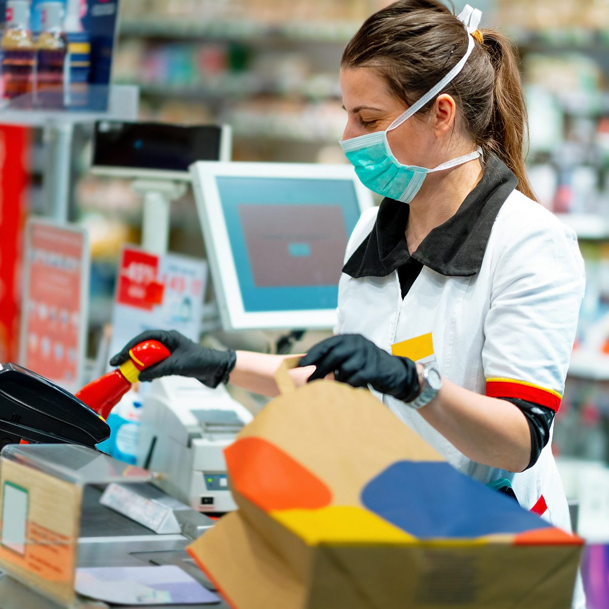 Woman cashier wearing protective face mask and gloves to prevent viruses, scanning disinfection products at the cash register and packing in paper bag