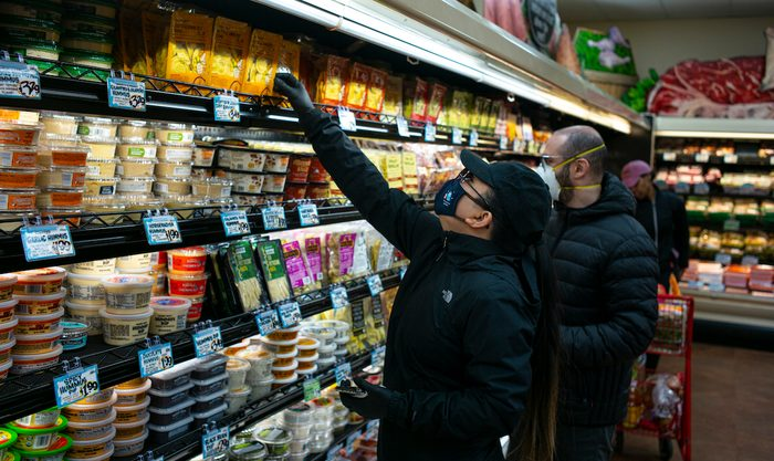 BROOKLYN, NEW YORK - MARCH 28: Shoppers wearing a surgical masks look at a prepared meals at a Trader Joes in Brooklyn, New York on March 28, 2020. The store lets in a minimum amount of shoppers at one time due to the spreading coronavirus. Trader Joes is an American chain of grocery stores headquartered in Monrovia, California. (Photo by Robert Nickelsberg/Getty Images)