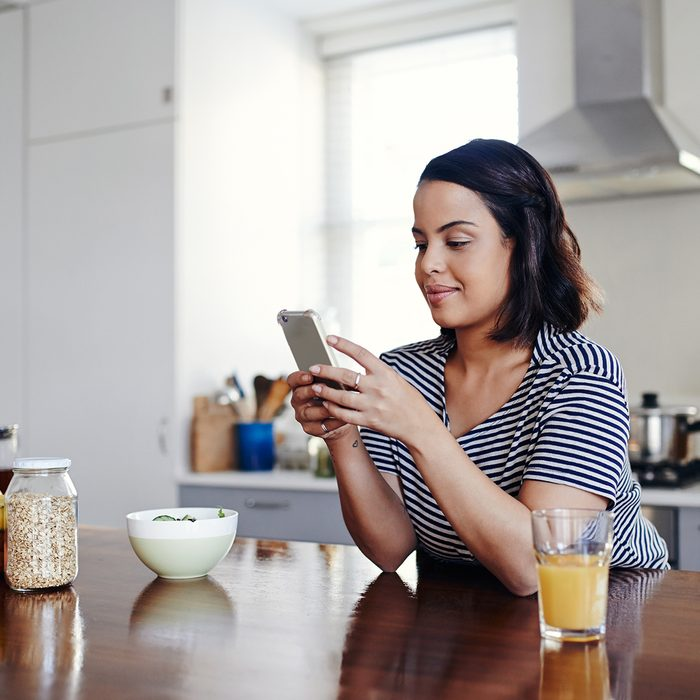 Shot of an attractive young woman using her cellphone at home