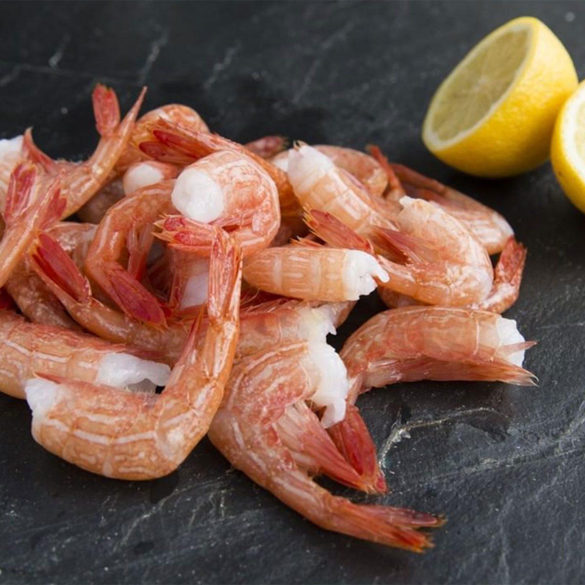 Shrimp beside a cut lemon