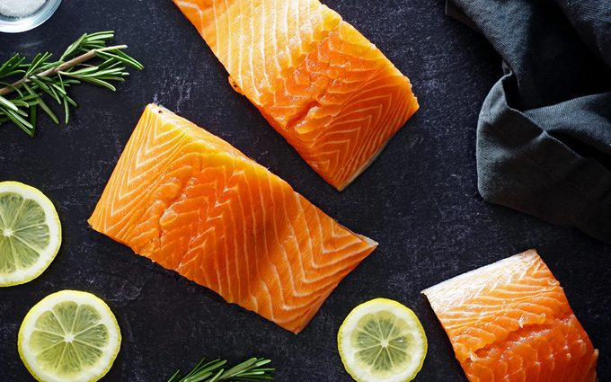 raw salmon on a slate counter with lemon slices and rosemary