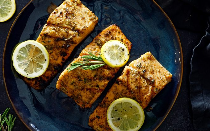 three grilled salmon fillets on a blue glazed plate garnished with lemon slices and fresh rosemary