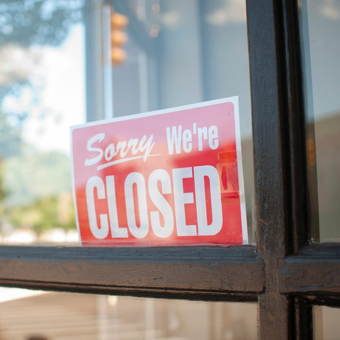 Sorry, We're Closed Sign in a small town main street storefront window.