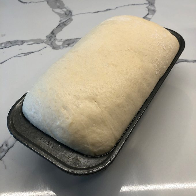 Dough having risen over the edge of the loaf pan
