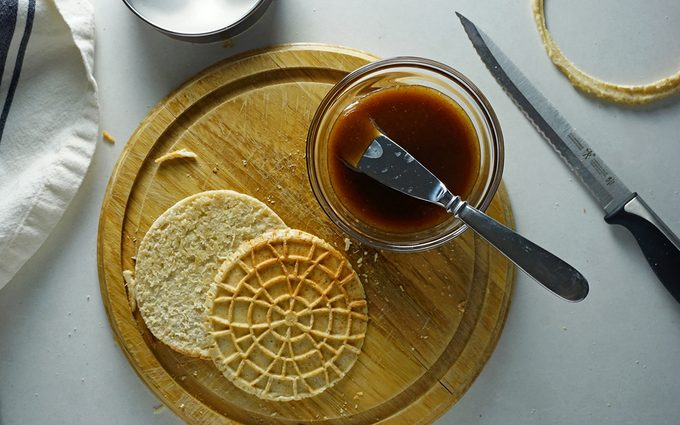 a sliced stroopwafel ready to have maple caramel filling spread on it