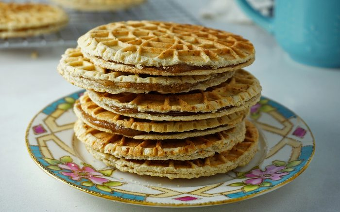 a stack of freshly made stroopwafels on a piece of china at an angle