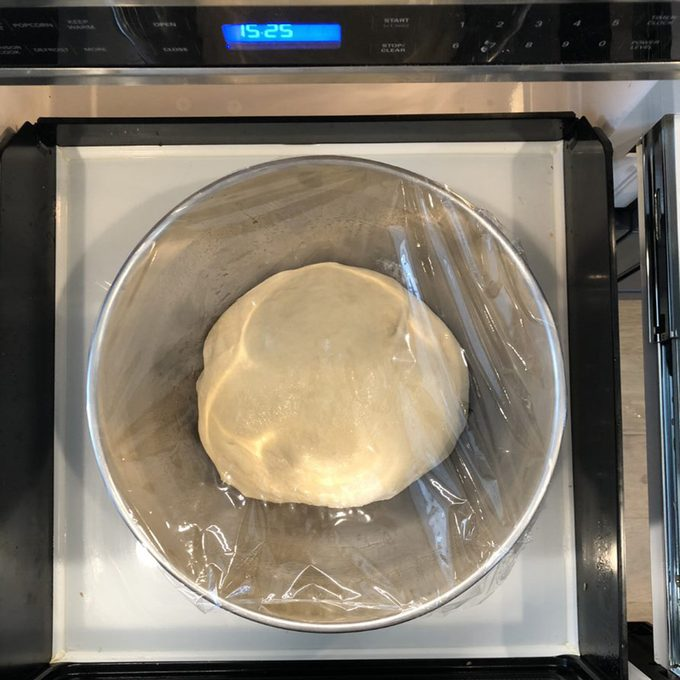 Dough rising in bowl covered with plastic wrap