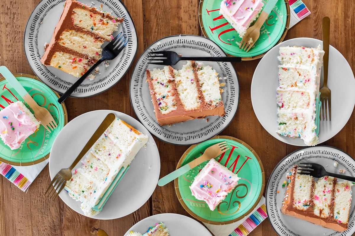 Many slices of cut birthday cake on a table.