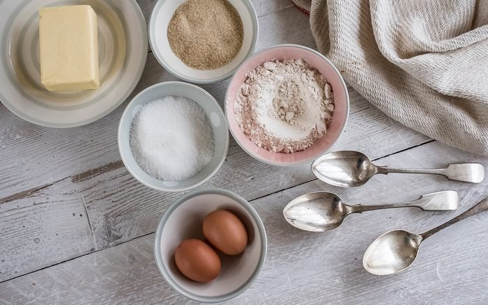 A table with ingredients for a baking project laid out, butter, sugar and flour, and two eggs.