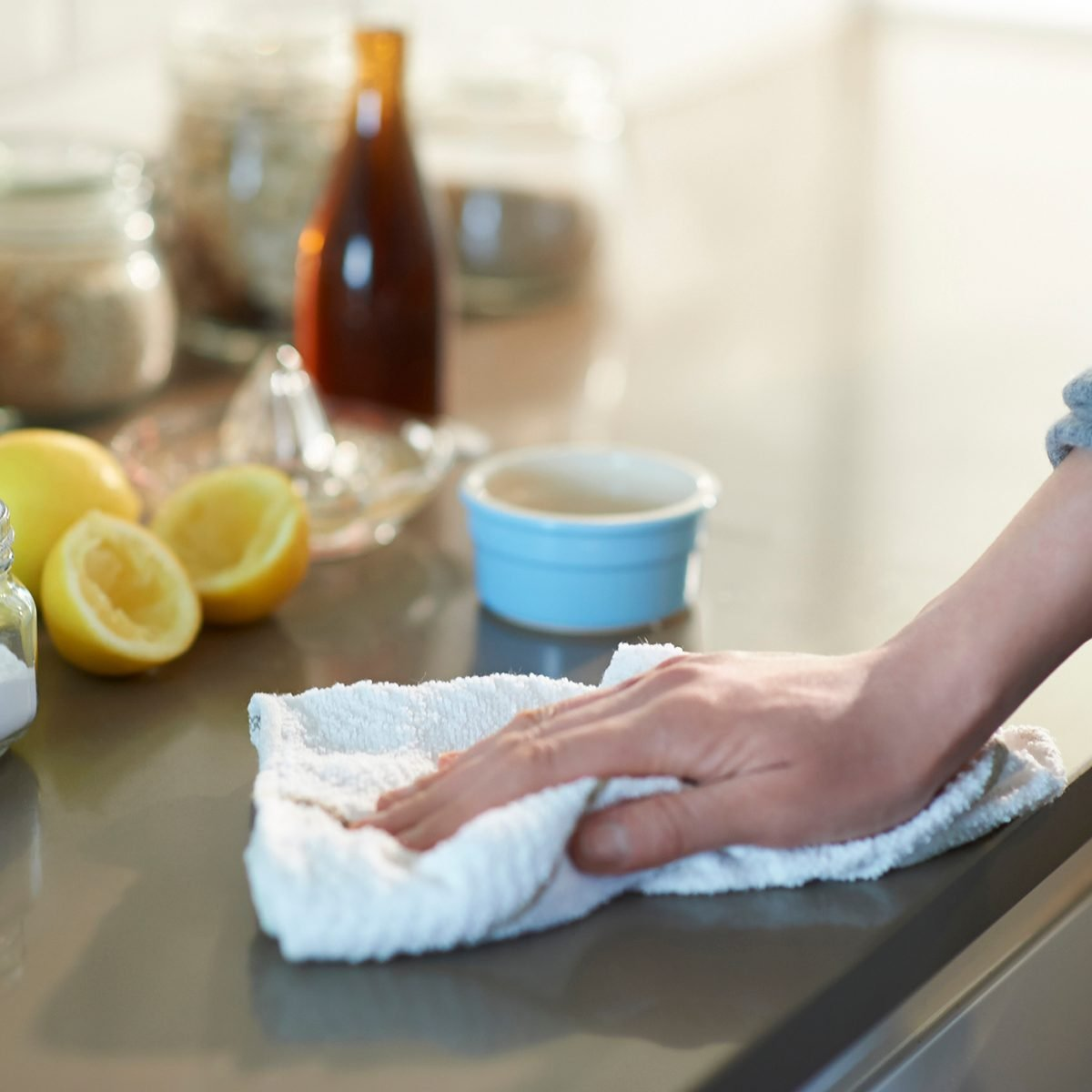 Woman cleaning a kitchen worktop with natural cleaning products lemon, bicarbonate of soda and vinegar.