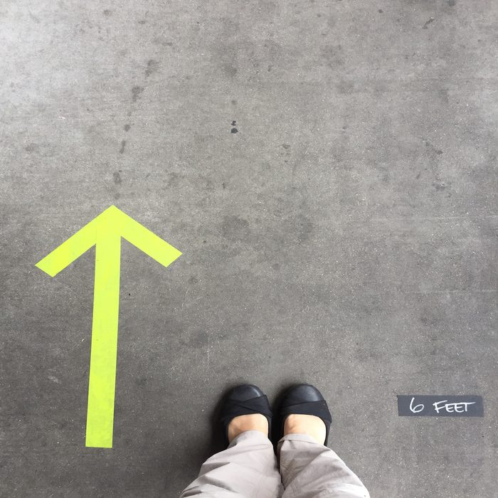6 feet distance and the one-way direction is marked outside of a store where customers are waiting in a line to enter the store.