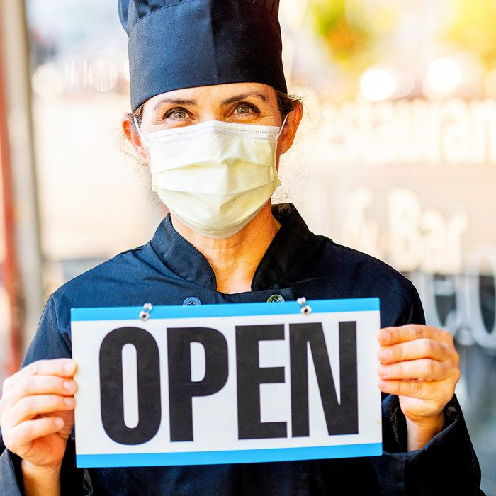 Female chef restaurant owner posing holding an Open Sign outside her restaurant wearing a mask because Covid-19