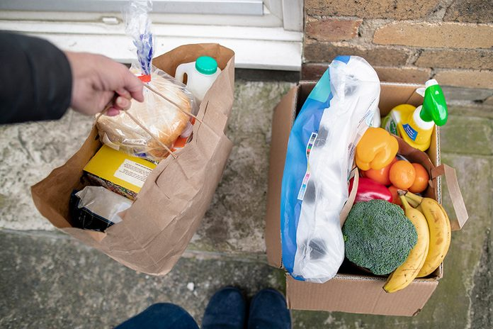 A point of view shot of a woman dropping off a box of groceries to her daughter and grandsons house, she leaves the box on the doorstep to avoid contact with her family.