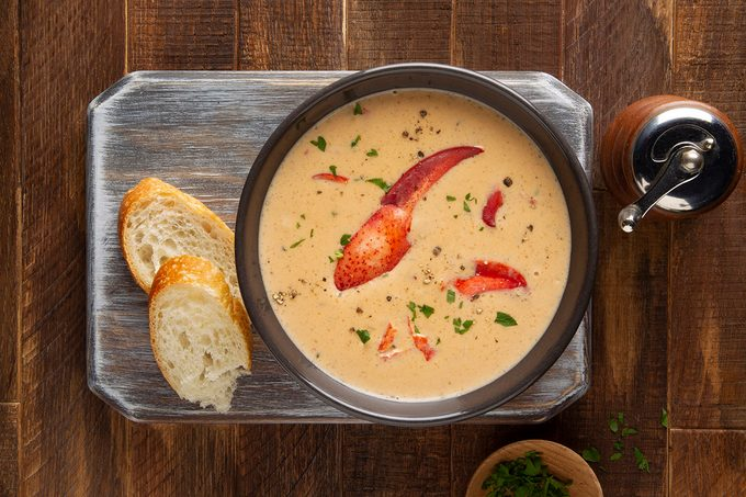 Homemade lobster bisque soup from scratch on table with bread.