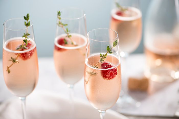 Flutes of pink rose champagne garnished with red raspberries and green thyme make for a festive cocktail gathering.