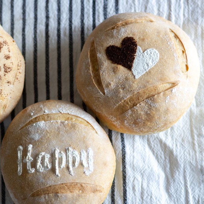 Stenciled bread loaves with white lettering and with white and chili powder hearts.