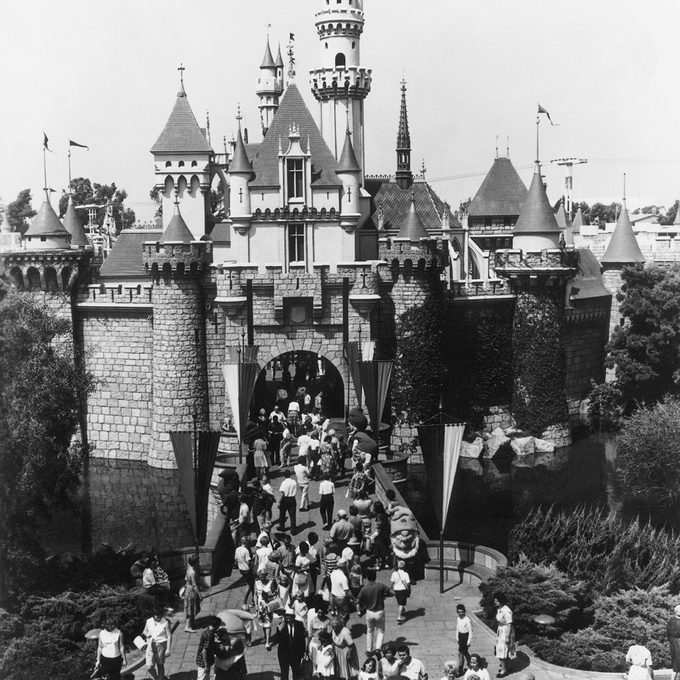UNITED STATES - JANUARY 01: 1955: Disneyland Welcome : What has become one of the best known landmarks of the wondrous world of Disneyland is this gateway to Sleeping Beauty's Castle. Through its portcullised arch lies Fantasyland, one of the five divisions of Disneyland. Greeting visitors on the castle drawbridge are Snow White and the seven Dwarfs, just a few of the famous Disney characters who inhabit this happy land. Some say that Las Vegas, an hour away by air, is a Disneyland for adults. (Photo by Keystone-France/Gamma-Keystone via Getty Images)