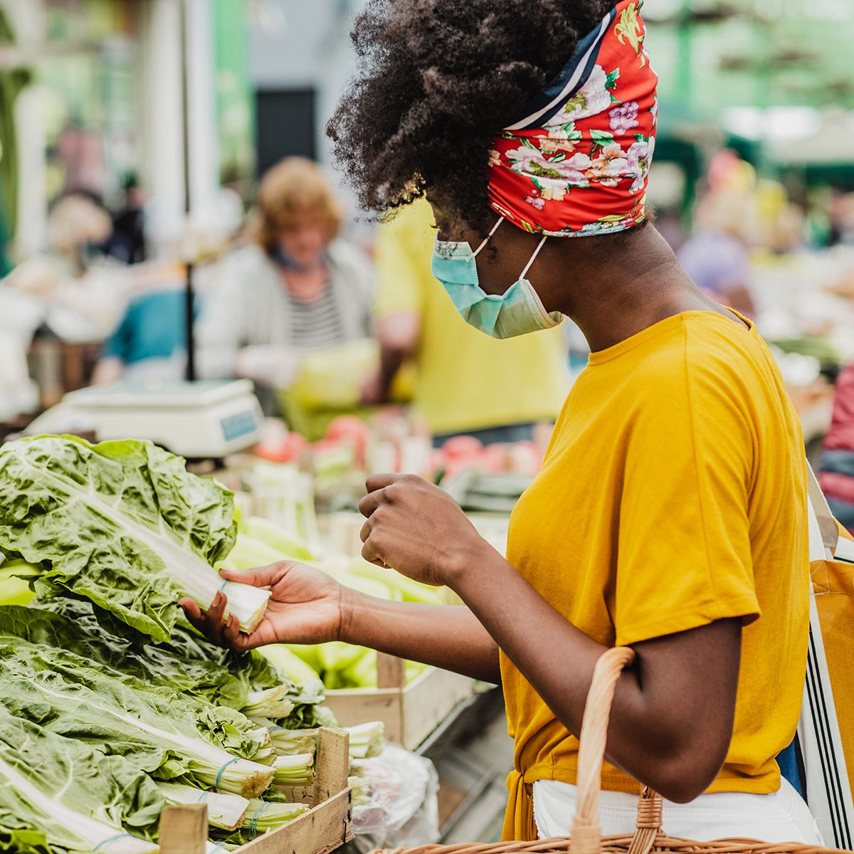 African American woman wearing a protective mask while buying groceries at the market