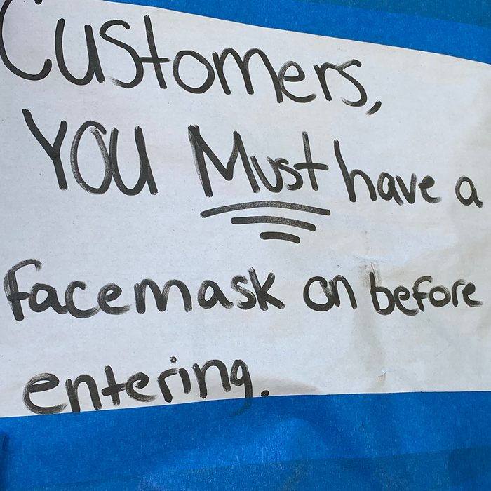 Close-up of a sign adhered on a small business commercial storefront window letting customers know in English that a protective face mask is required for entry.