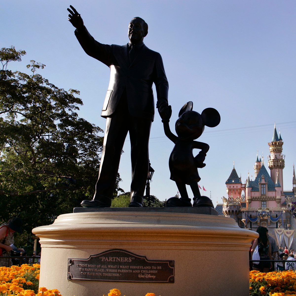 """Sleeping Beauty's Castle can be seen in the backround as people make their way past the """"Partners"""" statue (depicting Walt Disney and Mickey Mouse) at Disneyland, Friday July 15, 2005, in Anaheim. Disneyland celebrated its 50th anniversary on July 17, 2005. (Photo by Richard Hartog/Los Angeles Times via Getty Images)"""