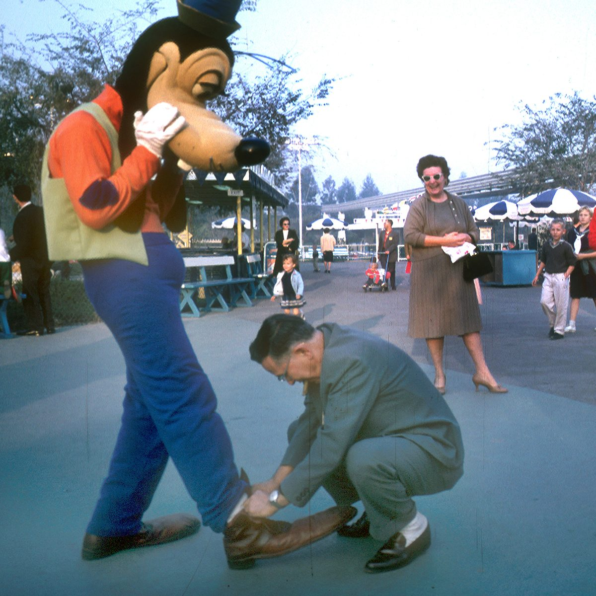 Disney character actor (played by photographer Tom Nebbia), dressed as Goofy, holds out his leg as a tourist ties his shoelaces at Disneyland, Anaheim, California, January 1962. (Photo by Tom Nebbia/Corbis via Getty Images)