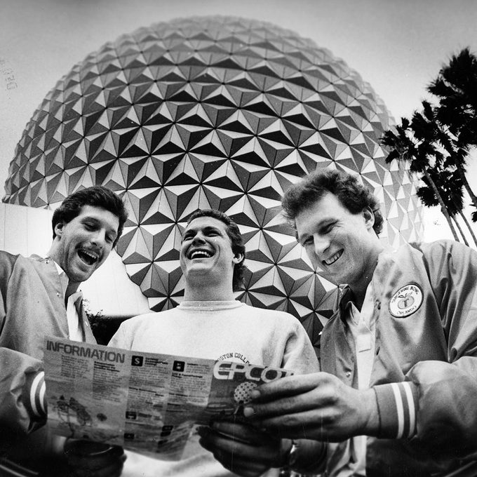 "ORLANDO, FL - DECEMBER 1: Standing in front of the ""Spaceship Earth"" globe at the EPCOT Center at Walt Disney World, Boston College players, form left, Jim Brown, Scott Nizolek and Brian Krystoforski check a map of the attractions while on tour, December 1982. BC was in town to play Auburn in the Tangerine Bowl. (Photo by John Tlumacki/The Boston Globe via Getty Images)"
