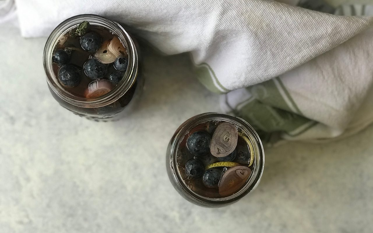 Filled jars of pickled blueberries, overhead