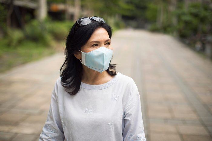 Portrait of a mature Taiwanese woman wearing protective mask over her mouth while walking the streets of Taipei.