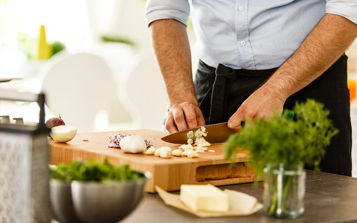 Chef slicing garlic on cutting board in the kitchen, preparing meal.