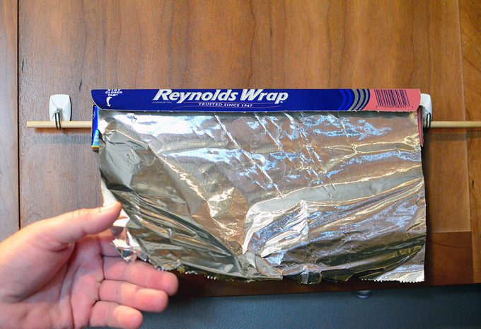 Man pulling foil off of DIY kitchen wrap storage organizer mounted on the back of a door.