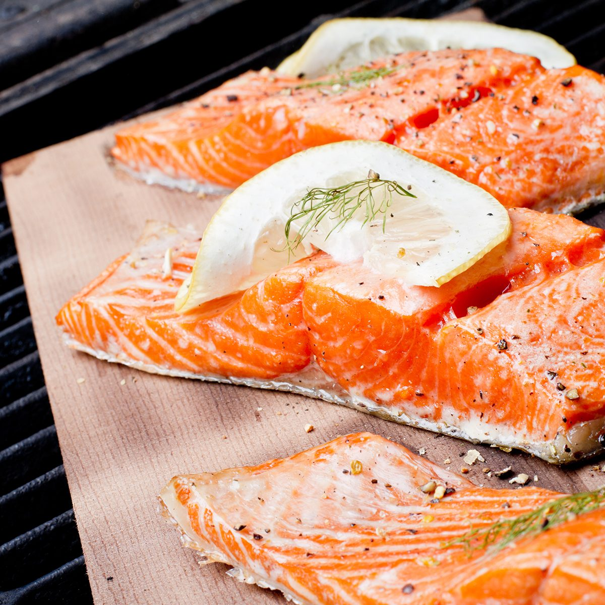 Three wild-caught salmon filets on a cedar plank in a backyard grill. Fist is bright reddish orange and is topped with lemon, dill and cracked pepper