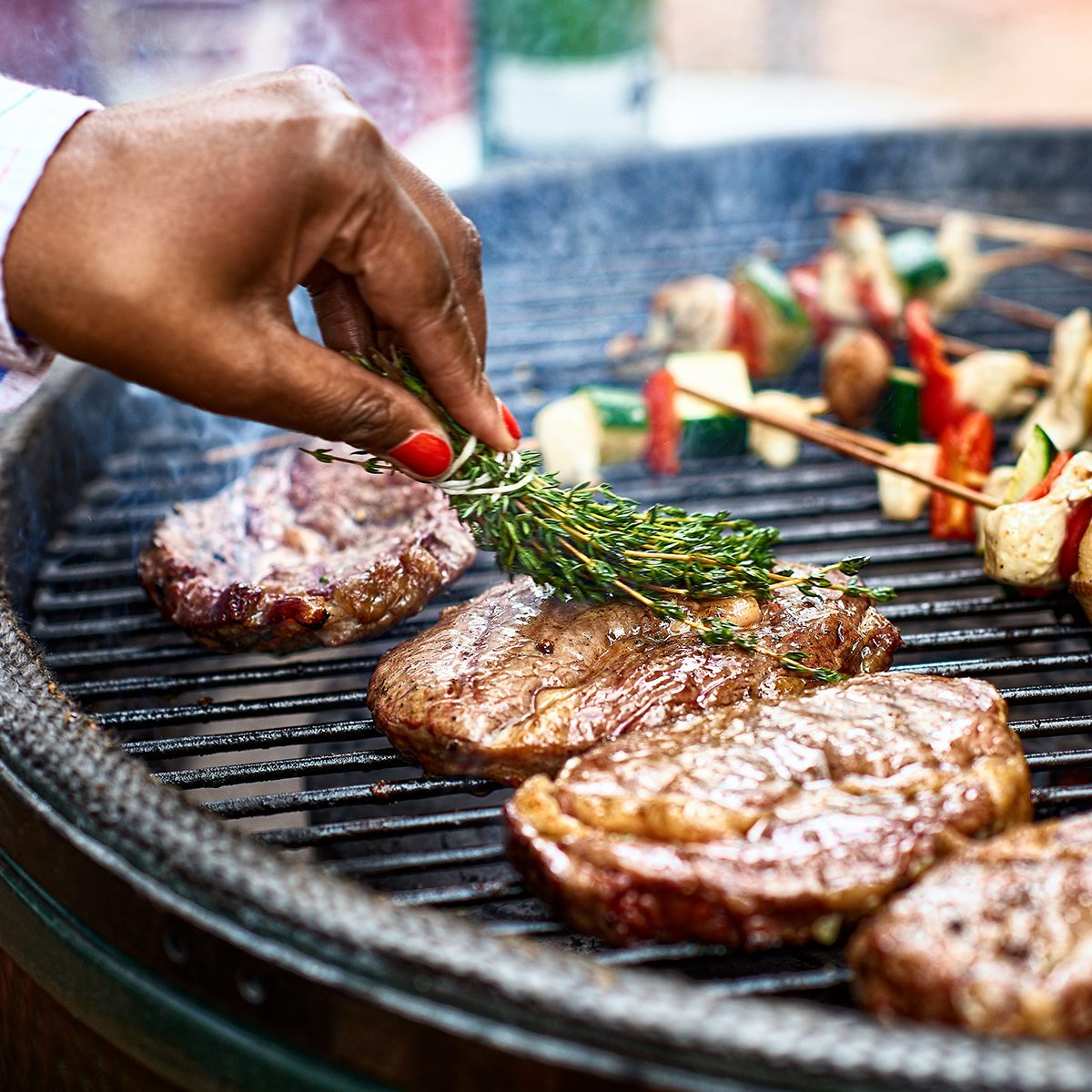 Steaks being seasoned with herbs as they cook on bbq grill with vegetable kebabs, mediterranean food, healthy lifestyle, food and drink