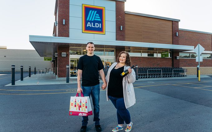 Aldi engagement couple in front of Aldi carrying groceries