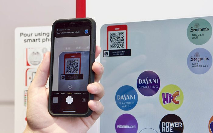 Person using phone and QR code on a soda machine