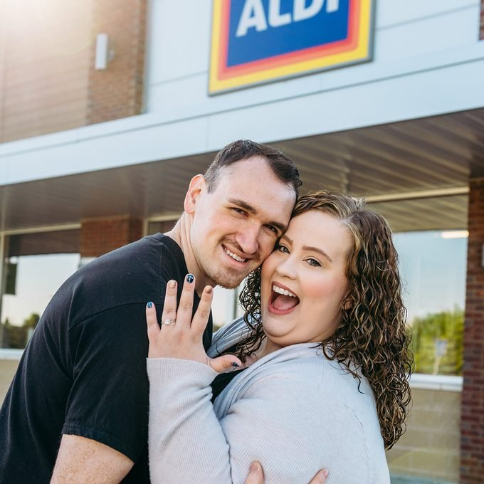 Aldi couple hugging in front of store