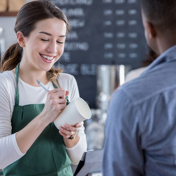 A smiling female coffee shop barista stands behind the checkout counter across from an unrecognizable patron. She looks down as she writes his order on a coffee cup.