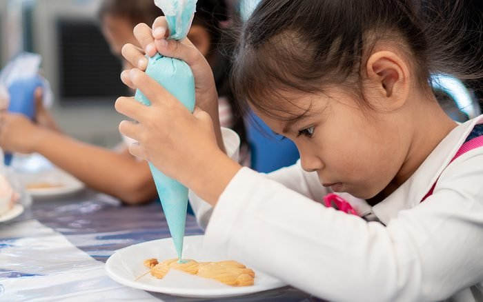 Cute asian child girl decorating cookies with fun
