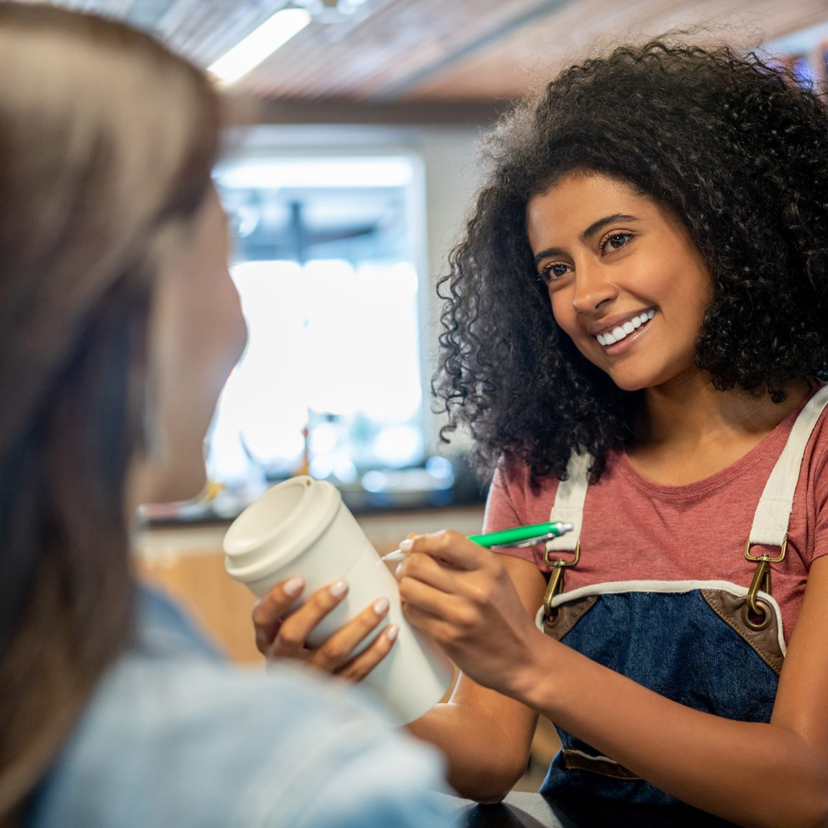 Friendly black waitress asking female customer her name to write on her coffee to go cup while smiling