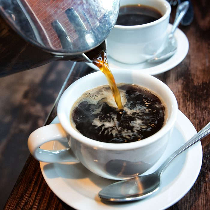 Fresh hot coffee being poured into a cup from a stainless steel french press in a trendy cafe