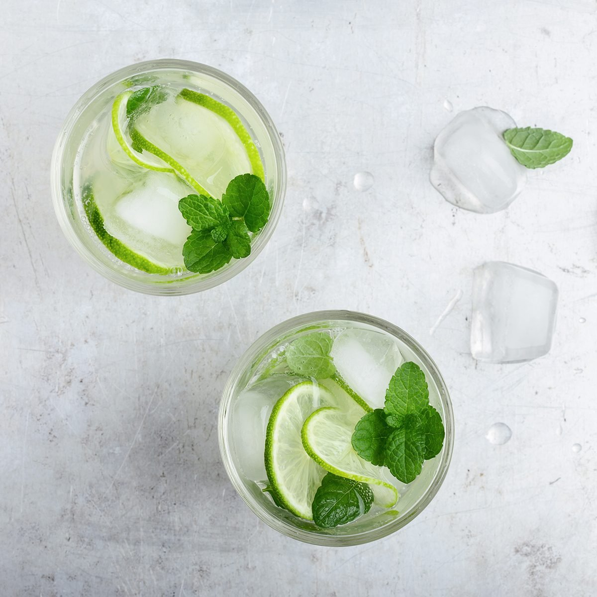Cold drinks. Glasses of homemade iced cold lemonade with fresh lime, juice and mint leaves, refreshing summer drink, top view