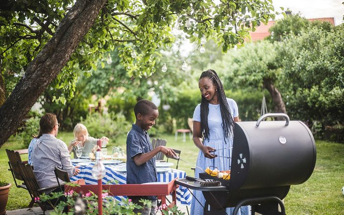 Mother and son preparing food on barbecue grill in yard during weekend party