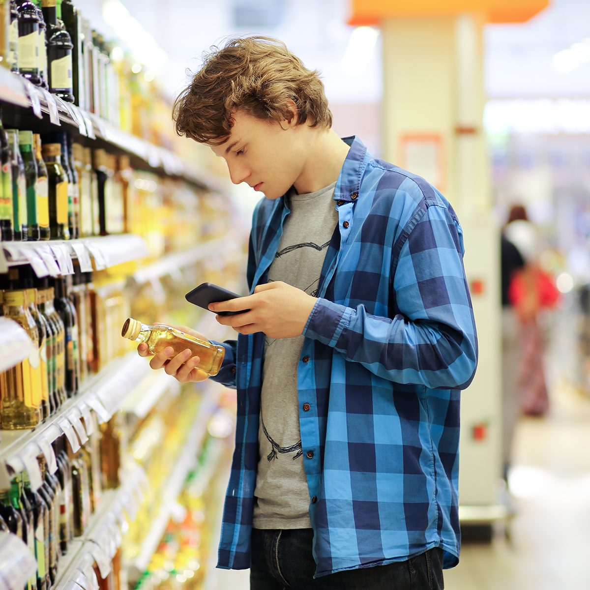 Man shopping in supermarket, reading product information