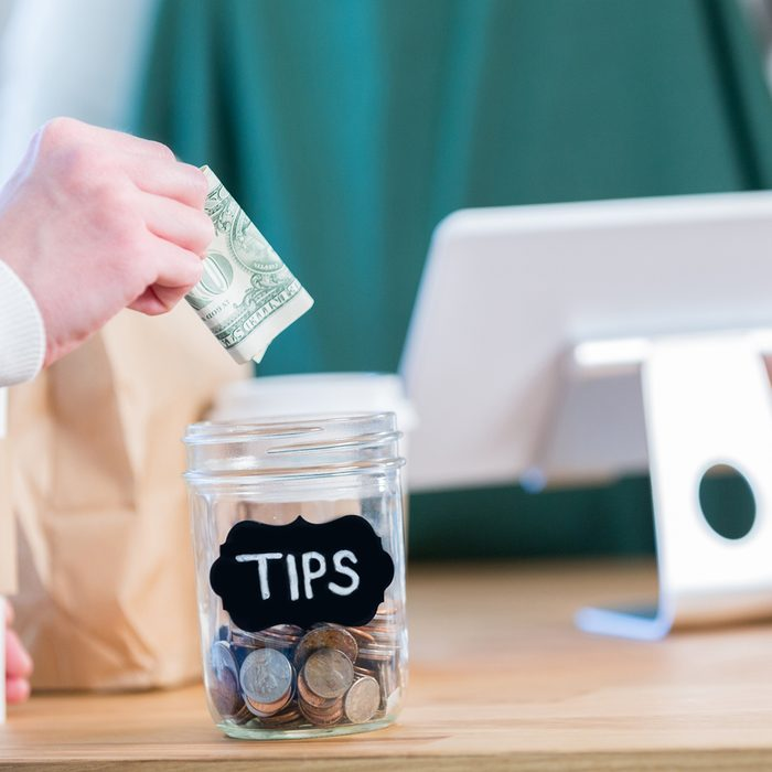 An unrecognizable coffee shop customer stands across the checkout counter from an unrecognizable barista and reaches out to put a paper bill in the tips jar.