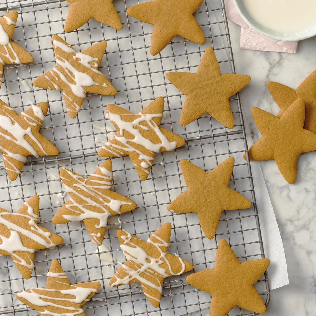 A wire rack with star-shaped cutout cookies cooling before they get drizzled with icing..
