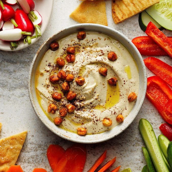 A bowl of homemade hummus topped with olive oil and roasted chickpeas.