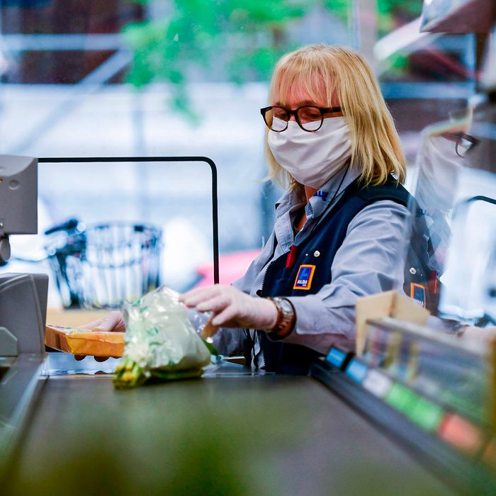 A cashier of food discounter ALDI wears a face mask as she serves a customer in Duesseldorf, western Germany, on April 29, 2020 amid the novel coronavirus COVID-19 pandemic. - From April 29, 2020 in Germany, masks are needed to enter shops, which began to open last week after the government declared its outbreak under control. Nose and mouth coverings are already compulsory on buses, trains and trams. (Photo by Ina FASSBENDER / AFP) (Photo by INA FASSBENDER/AFP via Getty Images)
